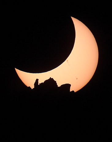 Eclipsed Sun setting behind The Shiprock